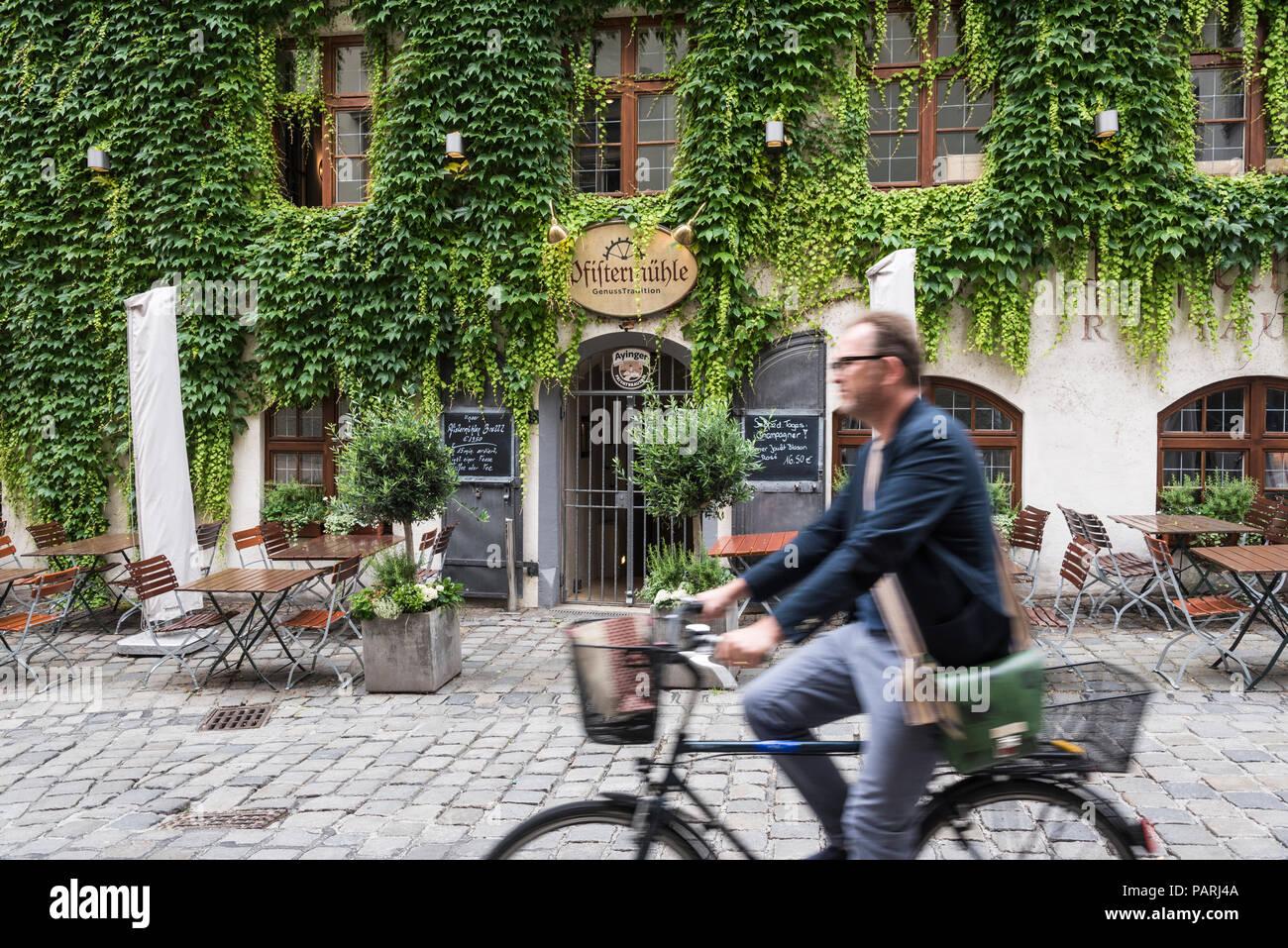 Uomo bicicletta equitazione da coperta di edera ristorante, Monaco di Baviera, Germania Immagini Stock