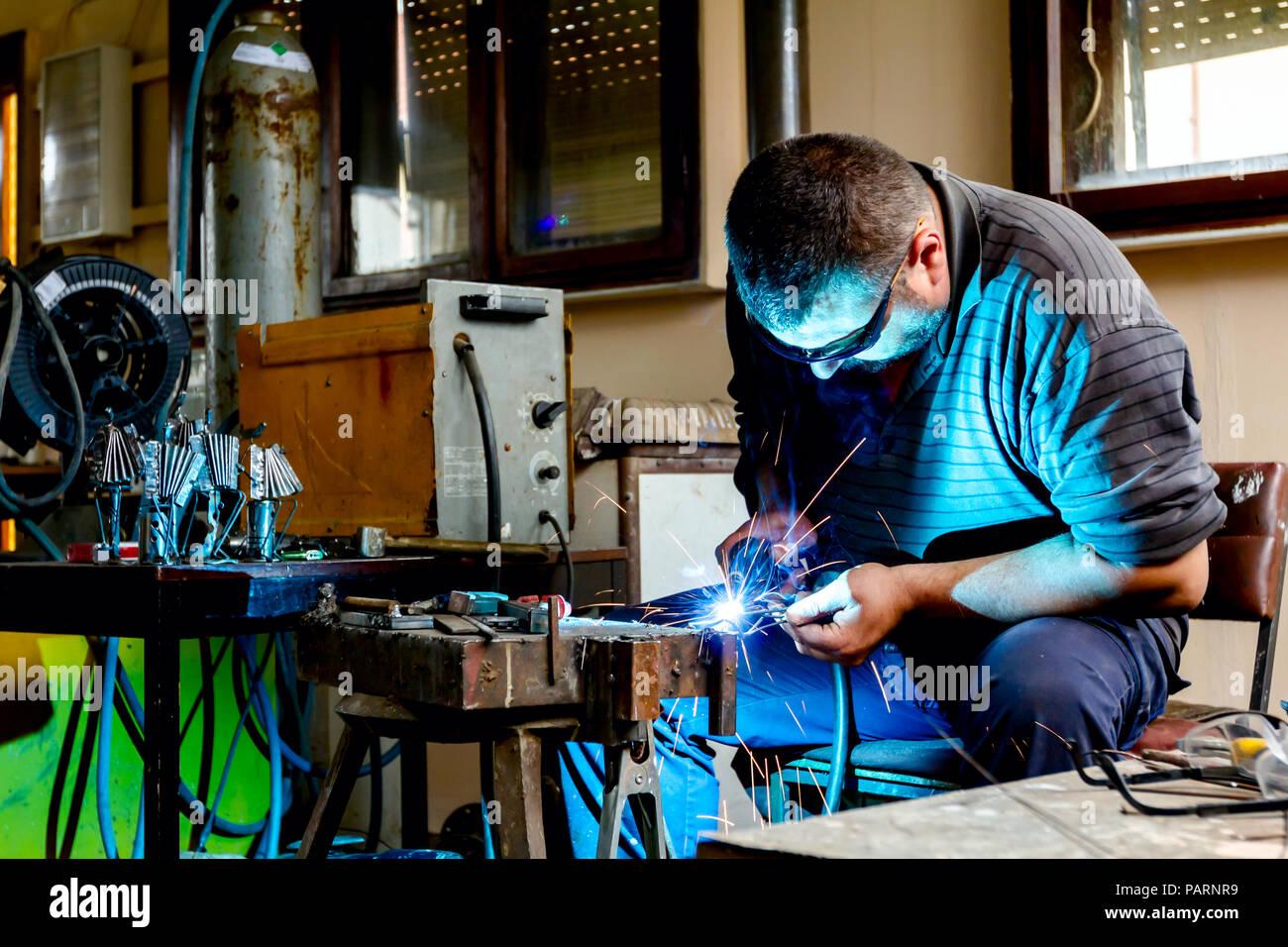 Scultore è tramite saldatura ad arco per gruppo di scultura di metallo barehanded con occhiali protettivi. Immagini Stock