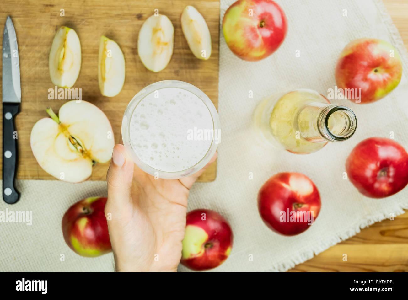 Lay piatto con un bicchiere di spumante di cidre drink sulla tavola in legno rustico. Il punto di vista della mano che trattiene il vetro del fatto in casa e sidro coltivati localmente organic Immagini Stock
