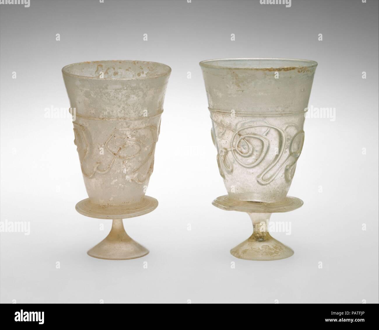 Coppe con decorazione applicata. Data: 11th-inizi del XII secolo. Questi matcing calici sono formate ciascuna da una coppa conica attaccato ad un piccolo, solido e strombate piede derivava da una flangia circolare applicata intorno alla base del bicchiere. Essi sono fatti di colore giallastro vetro incolore che contiene molte piccole bolle. Entrambe le coppe sono decorate con una ininterrotta sentiero applicata nello stesso colore giallognolo, che forma una linea orizzontale di circa due terzi dell'altezza e continua qui sotto per creare un fantasioso, configurazione astratta di parentesi progetta attorno al bicchiere. La decorazione può essere letto più chiaramente quando la coppa è Foto Stock