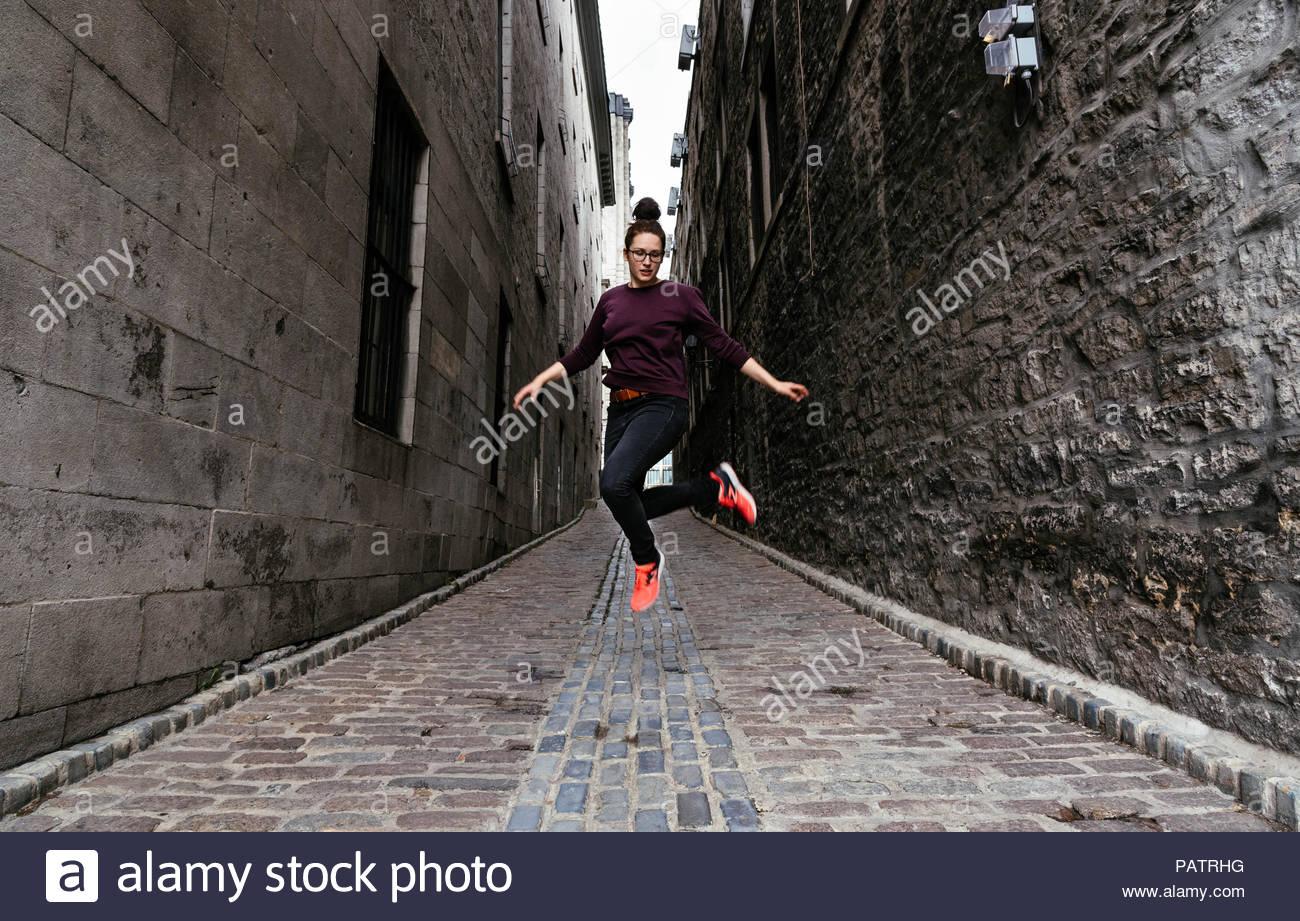 Azione girato di giovane donna saltando su strada di ciottoli Immagini Stock