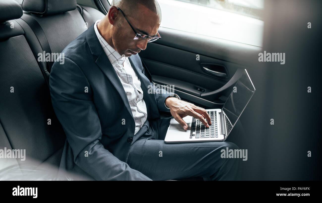 Imprenditore lavora su computer portatile durante gli spostamenti per ufficio nel suo sedan nel sedile posteriore. Imprenditore managing business lavoro in movimento in seduta Immagini Stock