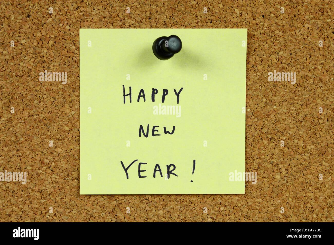 Giallo piccola nota adesiva su un ufficio cork bulletin board. Felice Anno Nuovo! Immagini Stock