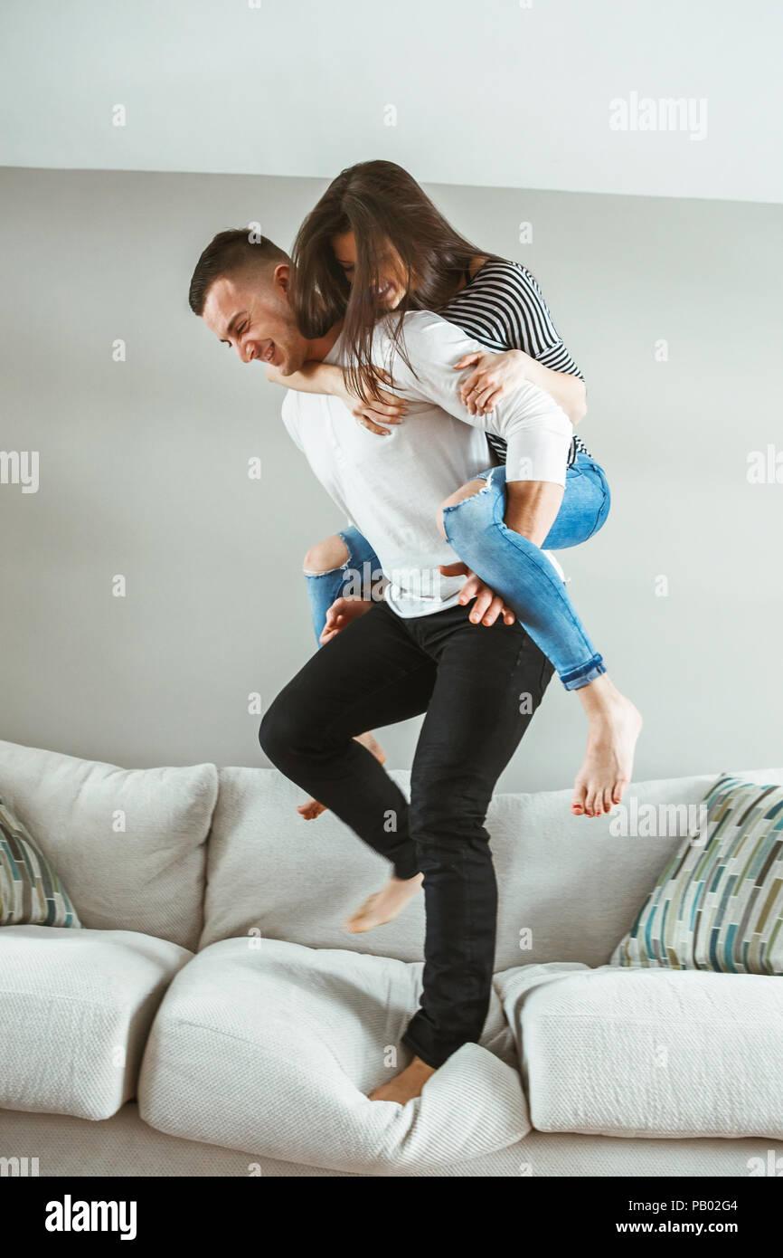 Ritratto di giovane bella funny giovane uomo donna in amore divertendosi in piedi sul letto sovrapponibile al chiuso in casa, tonica con filtri Immagini Stock
