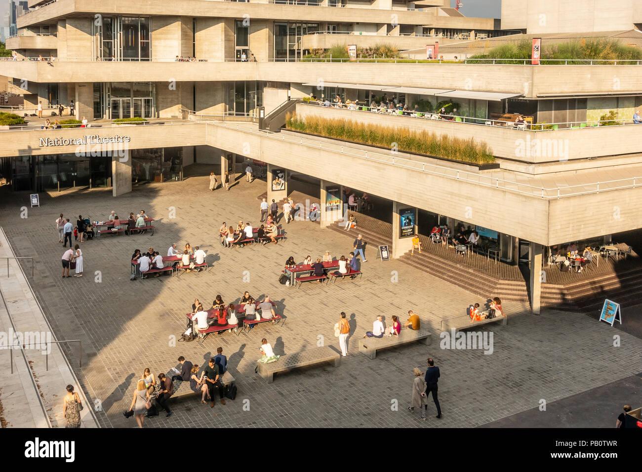 I turisti e i locali godendo di una calda sera di luglio al di fuori il calcestruzzo Brutalist architettura del Teatro Nazionale di Londra, Regno Unito Foto Stock