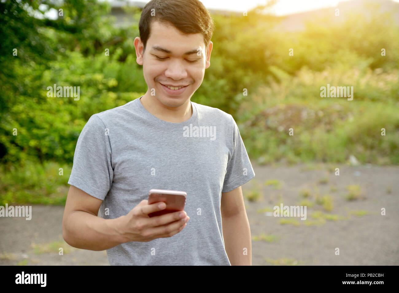 Uomo con smartphone e sorriso,l'uomo utilizzando il telefono cellulare per il lavoro e lo shopping da internet online Immagini Stock