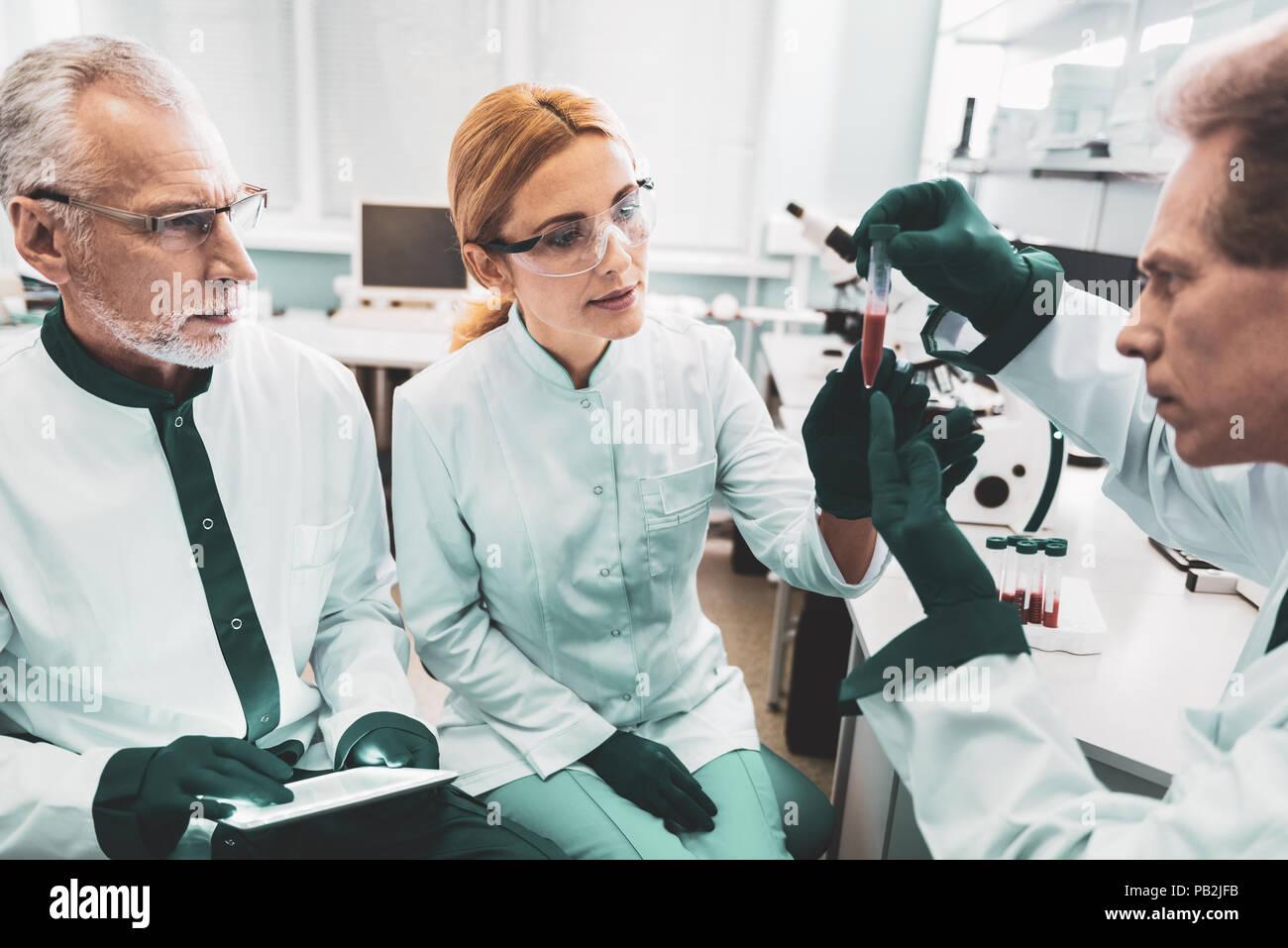 Tre farmacisti completamento analisi di medicina Immagini Stock