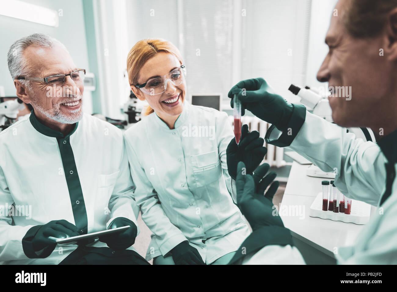 Il trio di sorridere lavoratori medici godendo di completamento attività Immagini Stock