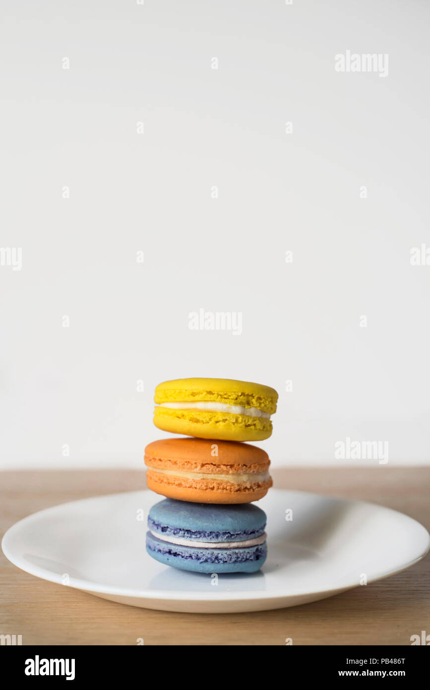 Un Pile-Up di Macarons in tre colori - Bright beni cotti al forno Trio su una piastra Immagini Stock
