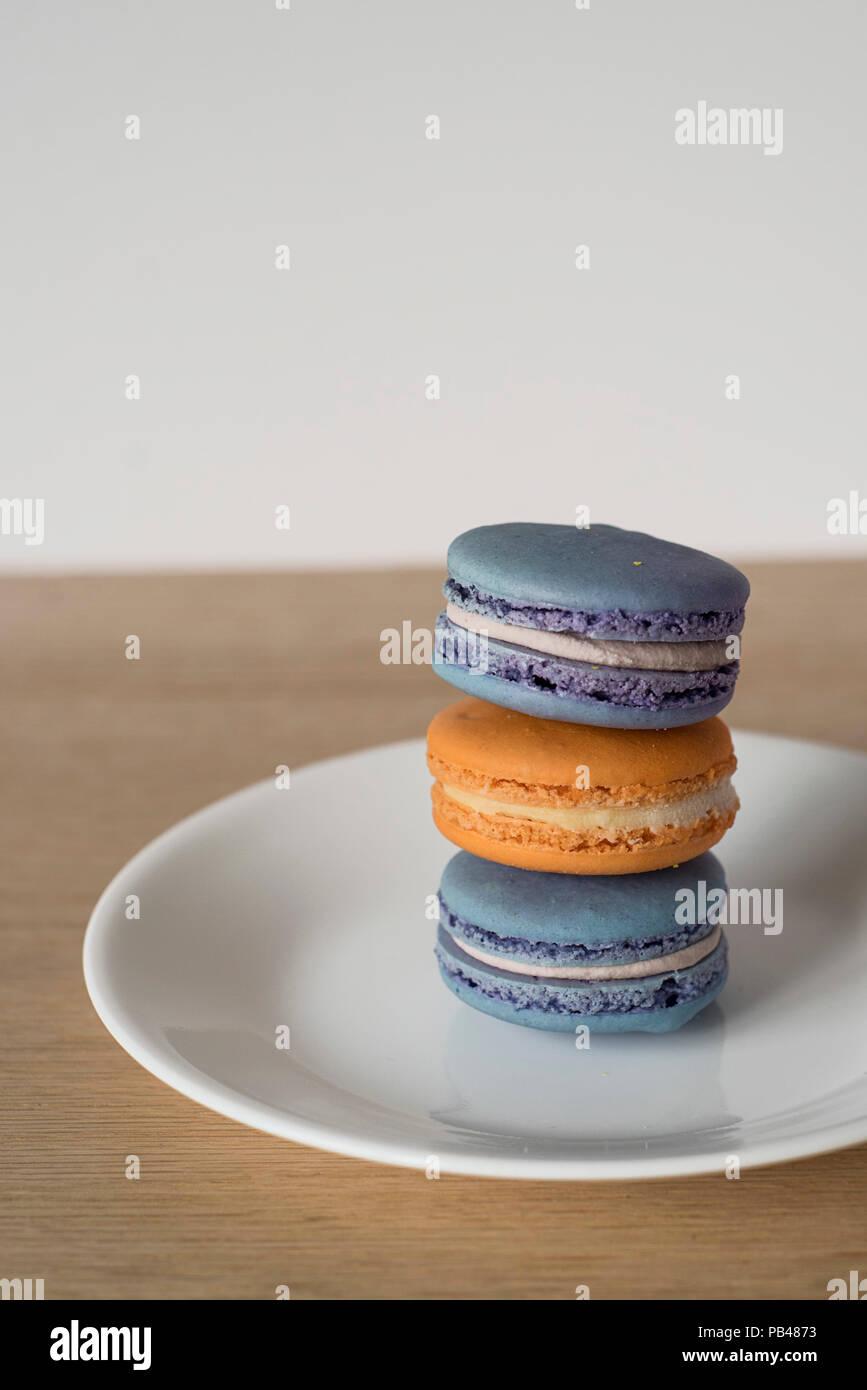 Pila di amaretti francese / Macarons in blu e arancione, una golosa e spuntino zuccherino Immagini Stock