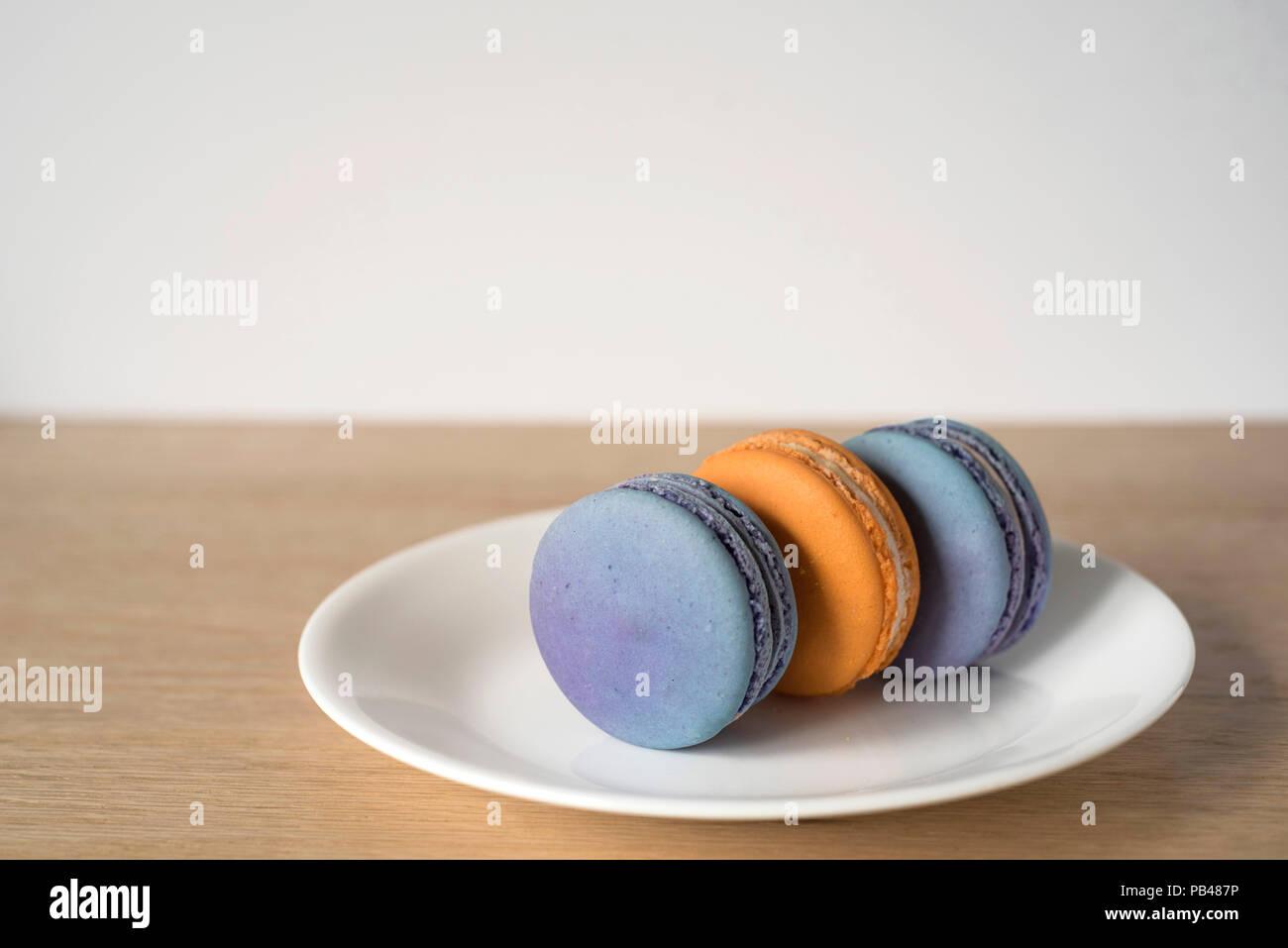 Tre arancio e blu Macarons seduti sui loro lati su una piastra Immagini Stock