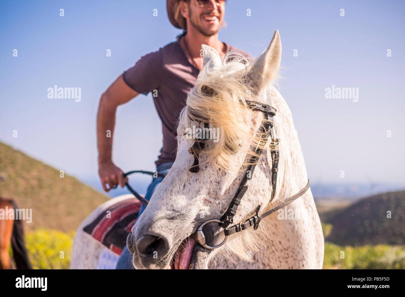 L uomo moderno cowboy godono di una naturale e uno stile di vita alternativo in sella ad un cavallo bianco. amicizia e natura outdoor per belle persone che vivono a differenti Immagini Stock