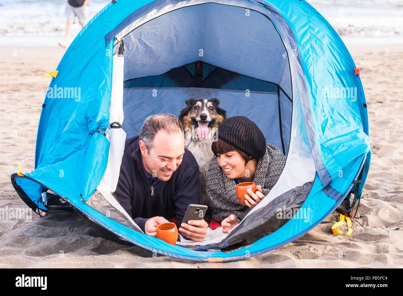 Giovane guardando la smart phone e divertirsi dentro una tenda in campeggio libero sulla spiaggia cane Border Collie dietro di loro guardando la telecamera. vintage Immagini Stock