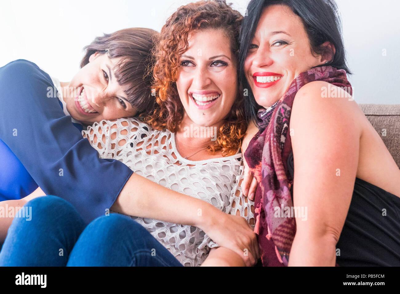 Allegro femmine età media giovani amici womane insieme seduta su un divano a casa in attività del tempo libero indoor. sorriso e godersi la giornata e abbraccia a Immagini Stock