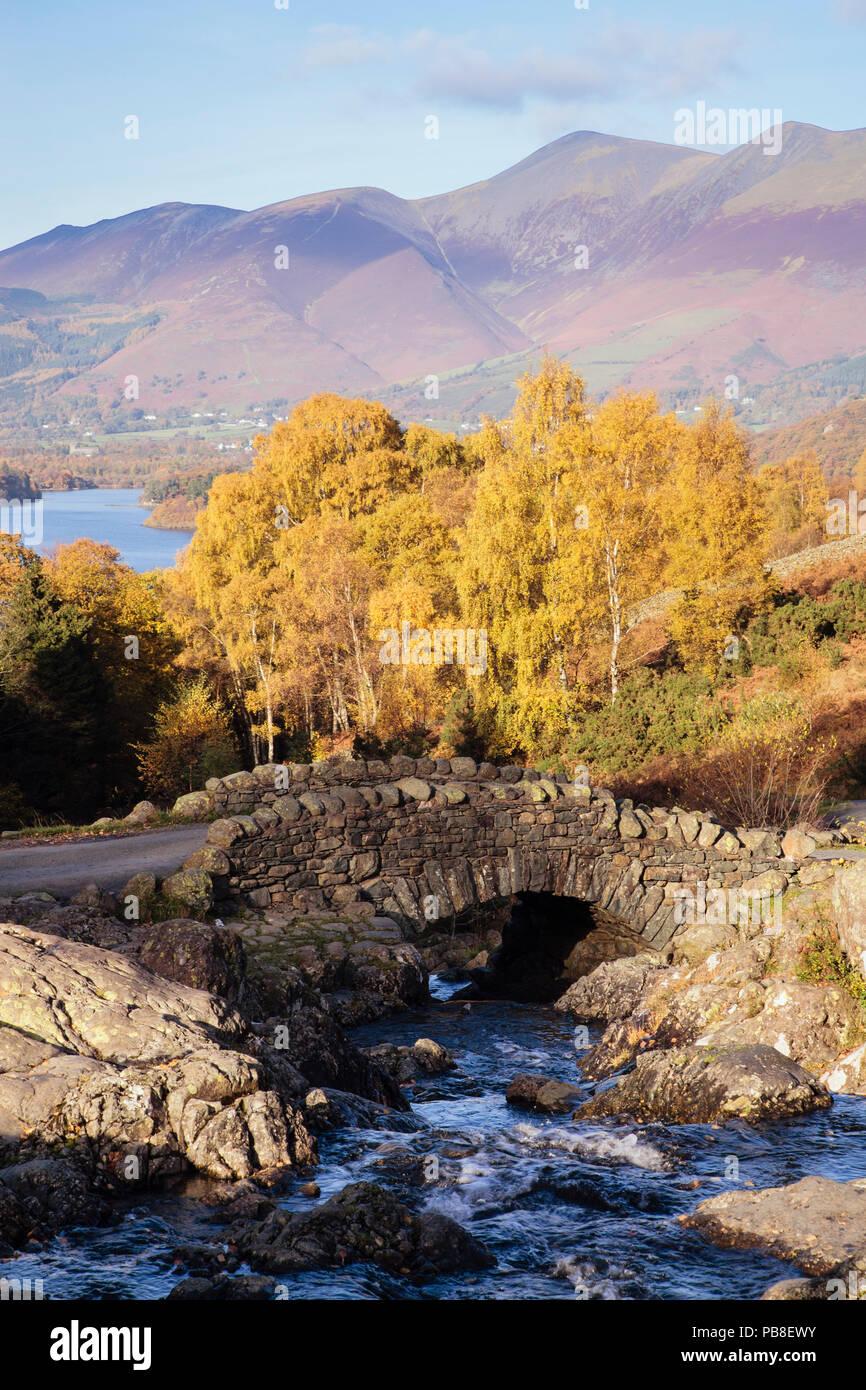 Ponte Ashness e flusso con alberi in autunno, Derwent Water e Skiddaw al di là della montagna nel Parco Nazionale del Distretto dei Laghi. Keswick Cumbria Inghilterra England Regno Unito Immagini Stock