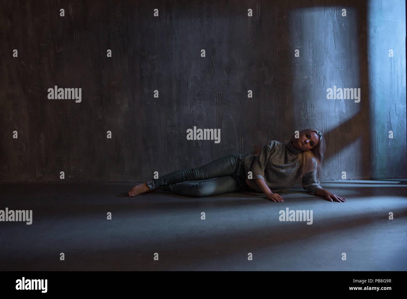 PTSD. Giovane donna sdraiata sul pavimento, concetto di problema psicologico Immagini Stock