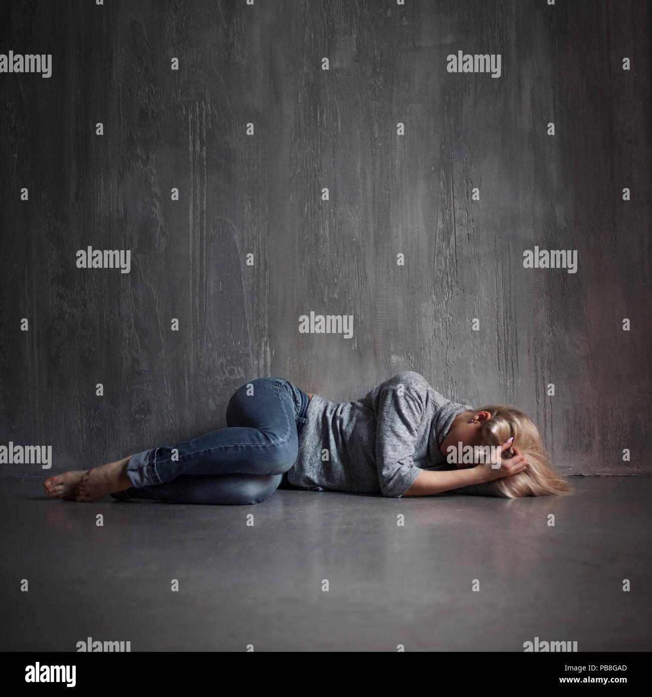 La depressione. Giovane donna sdraiata sul pavimento che copre la testa con le mani, il concetto di stress, copia spazio sulla parte superiore Immagini Stock