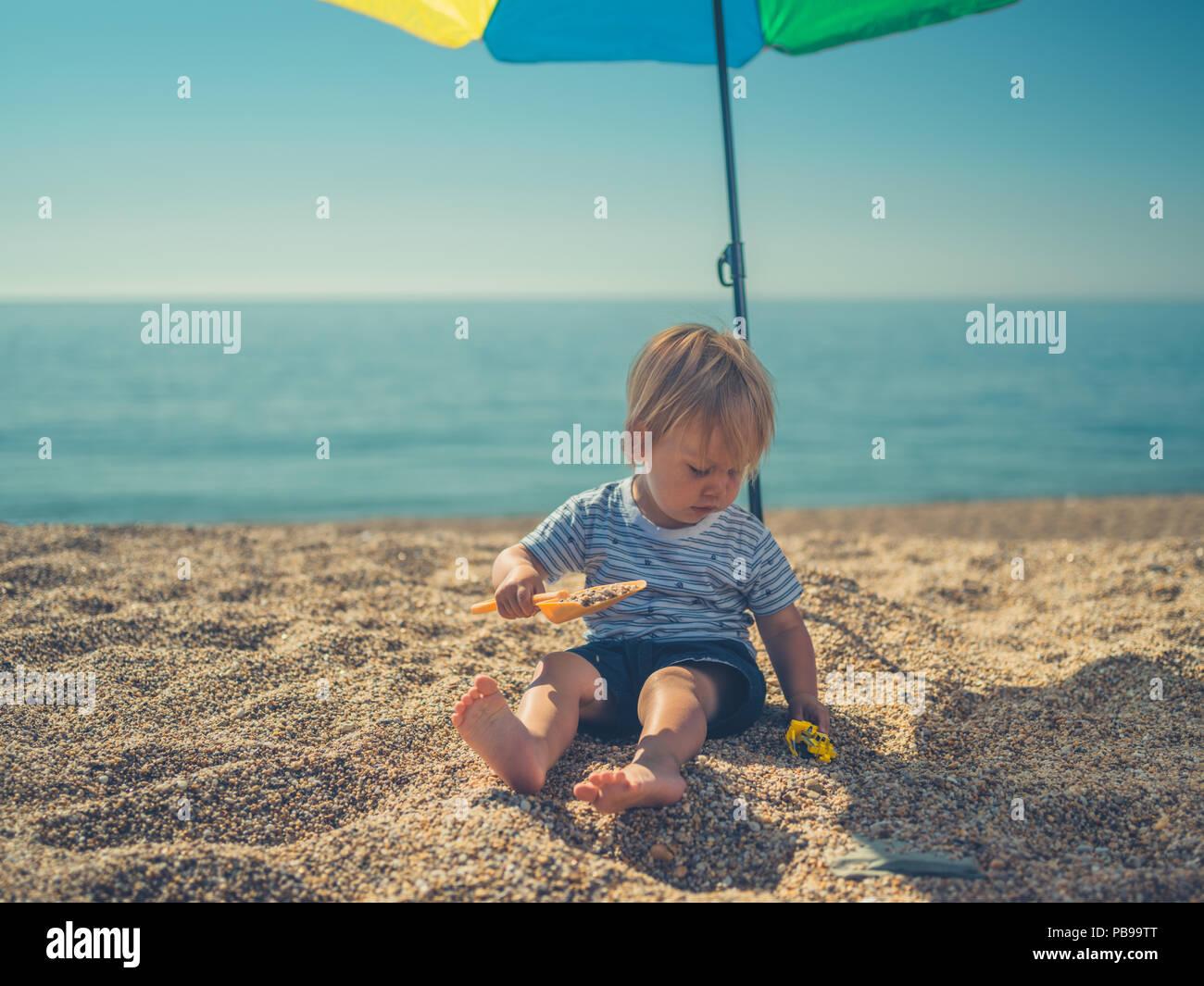 Ombrellone Piccolo Da Spiaggia.Un Piccolo Bambino E Seduto Da Se Stesso Sotto Un Ombrellone