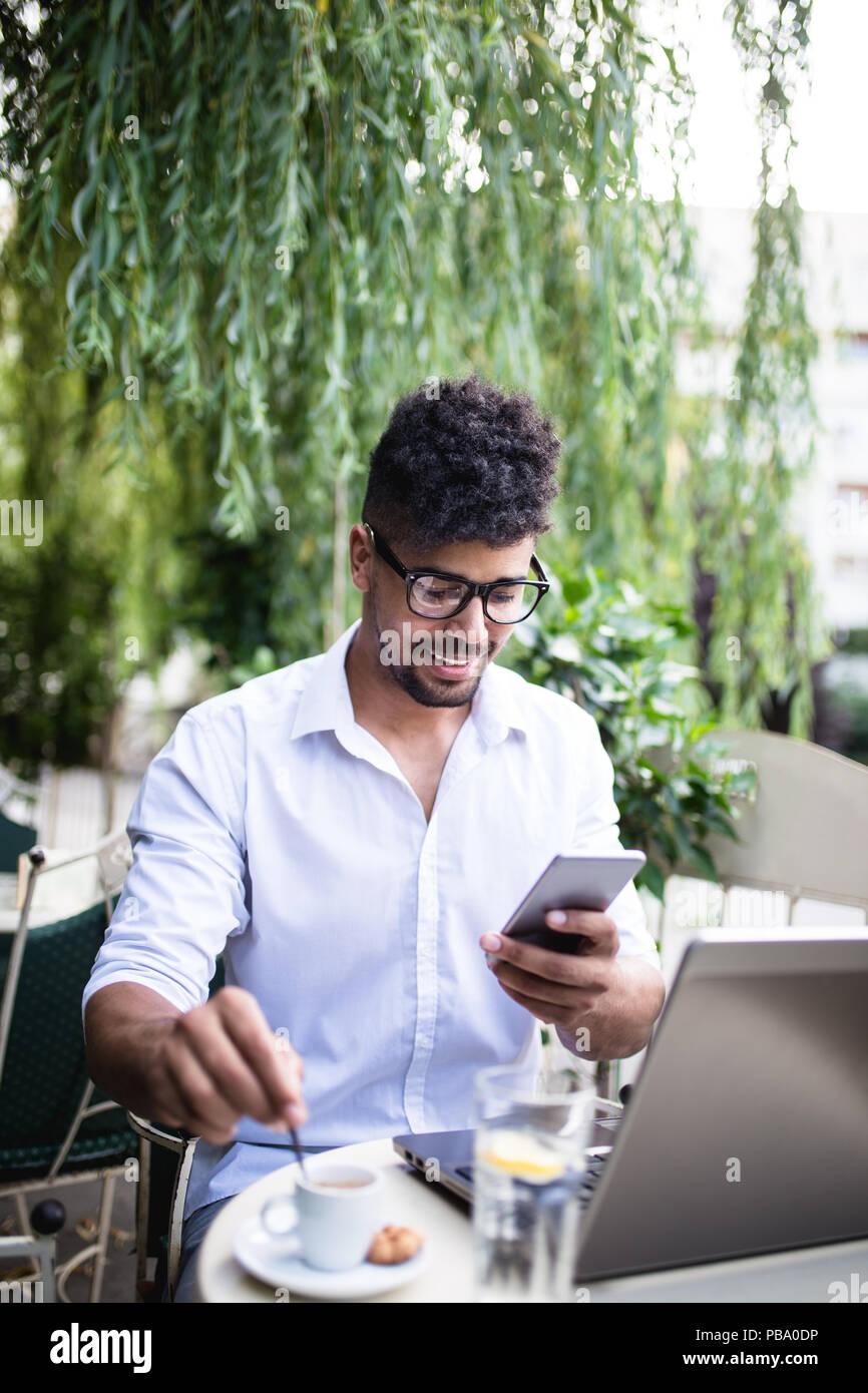 Giovani attraenti Afro American businessman in seduta cafe bar, a bere caffè e facendo qualche lavoro sul computer portatile. Foto Stock