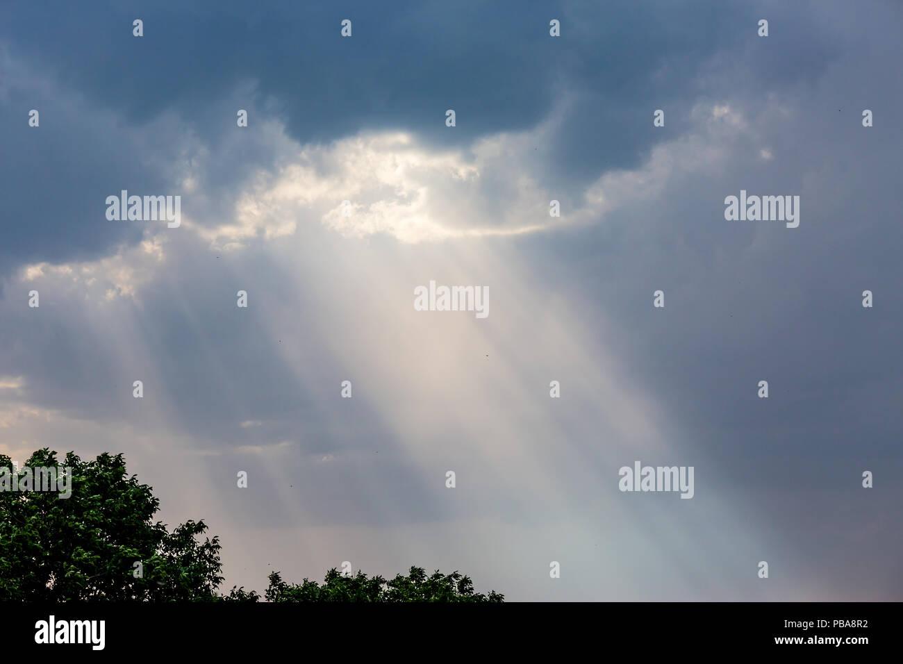 Raggi di luci proveniente attraverso le nuvole scure appena prima di heavy rain, luce divina dal cielo Immagini Stock