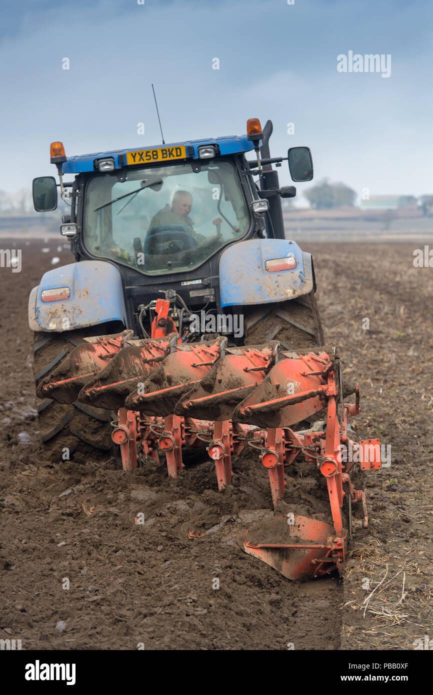 L'aratura di un campo con una New Holland T7030 e un solco 5 reversibile aratro Kuhn, voce di distanza. North Yorkshire, Regno Unito. Foto Stock