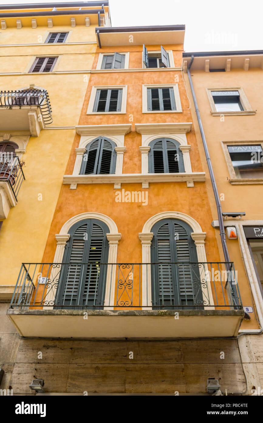 Luminoso giallo senape balcone italiano con finestre a doppi vetri e chiuso per persiane di - Finestre con persiane ...