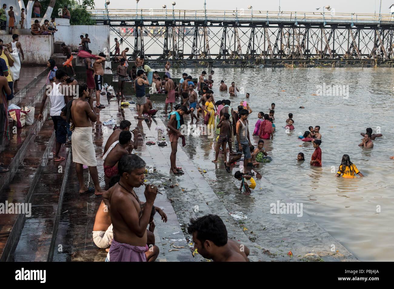 Persone si bagnano nelle acque del fiume Hoogly (Gange), vicino a quella di Howrah (vecchio) ponte, Calcutta, West Bengal, India Immagini Stock