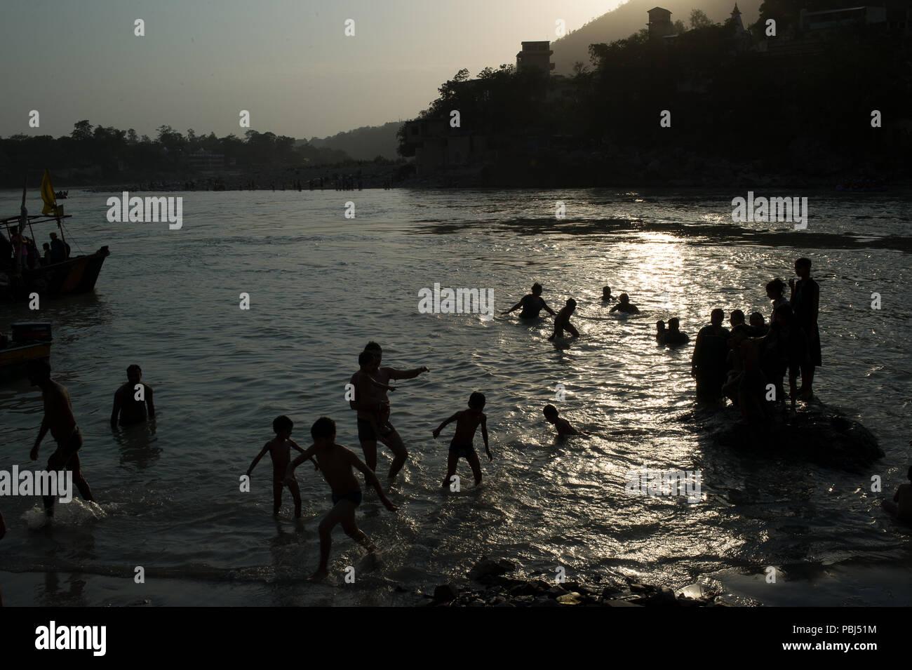 Persone si bagnano nel sacro Gange fiume al tramonto, Rishikesh, India, Asia Immagini Stock