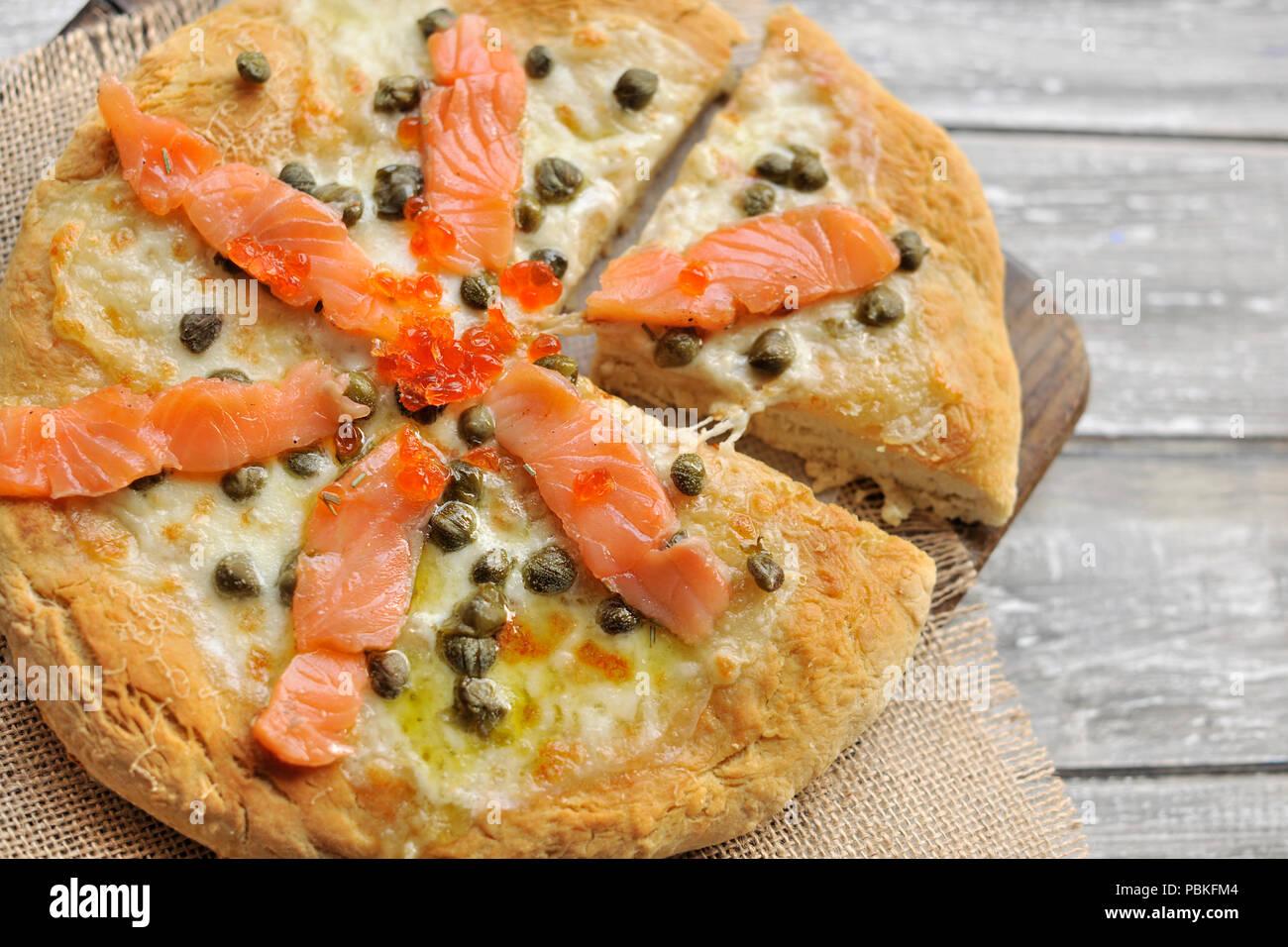 Pizza con salmone e basilico e capperi. Tradizionale pasticceria italiana. Spazio di copia Immagini Stock