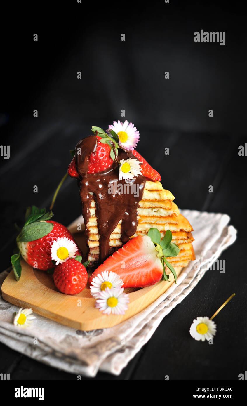 Pancake con fragole e cioccolato, deliziosa colazione casalinga. Immagini Stock