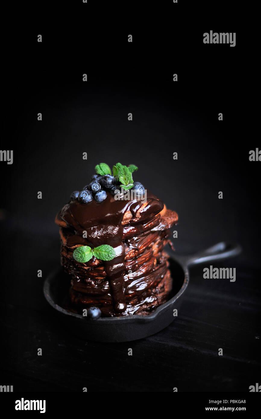 Frittelle al cioccolato per colazione con mirtilli, scuro foto. In casa la cottura. Immagini Stock