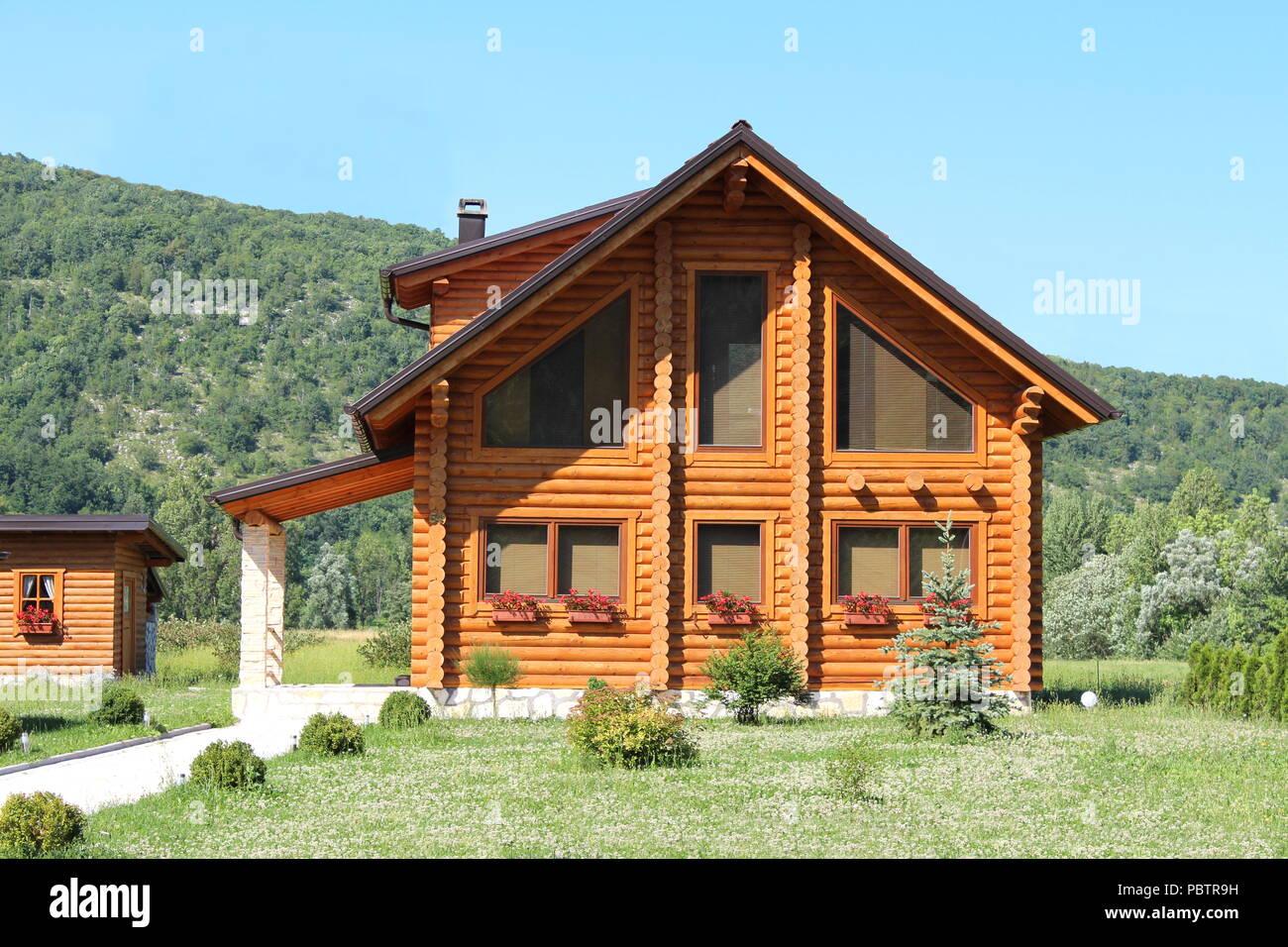 Di recente costruzione in legno log cabin casa con grandi finestre e entrata in pietra circondato da erba non tagliata piena di piccoli fiori e foresta con blu chiaro Immagini Stock