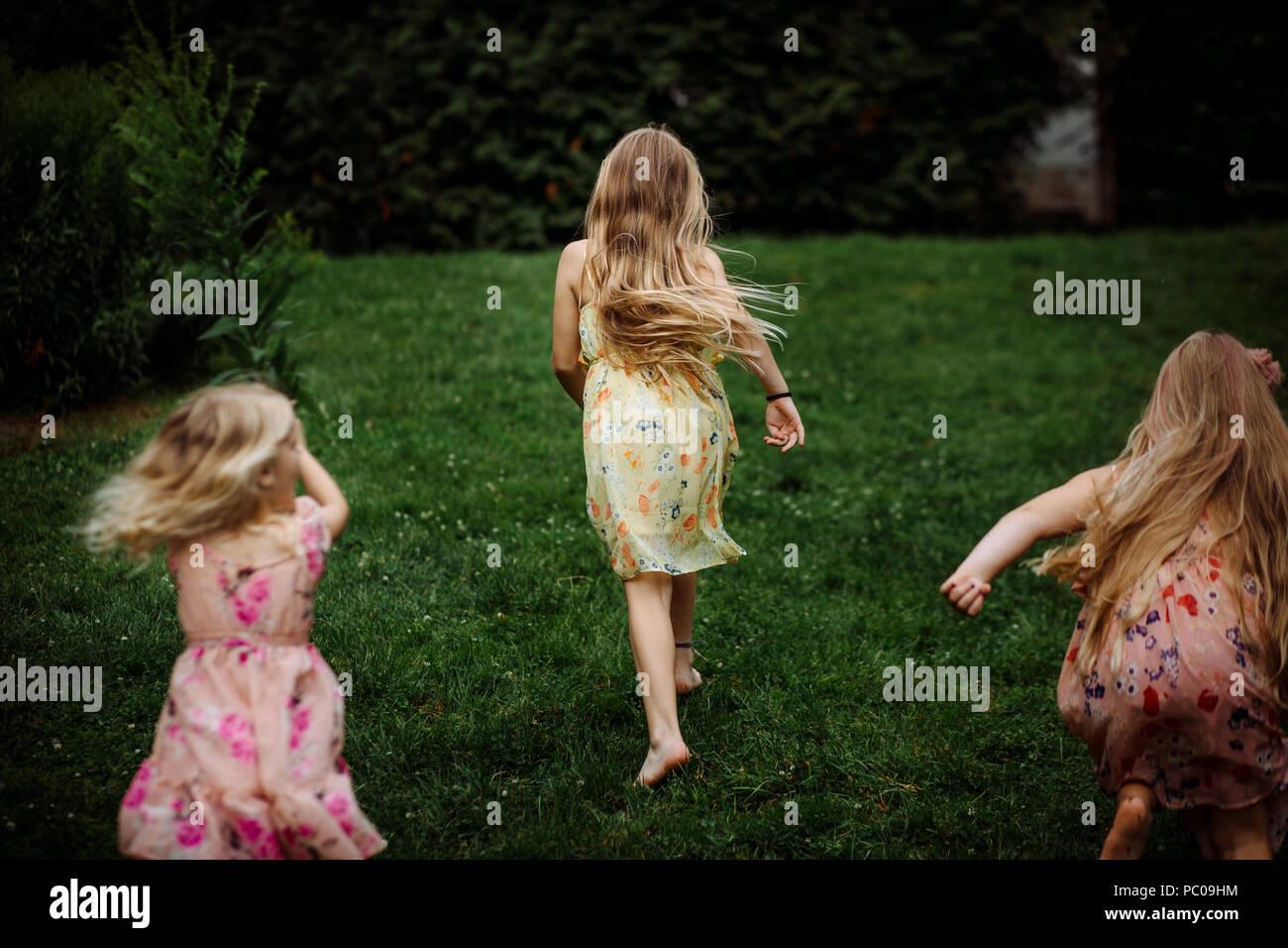 La comparsa di tre piccoli ragazze vestito con un abito in esecuzione nel parco Immagini Stock