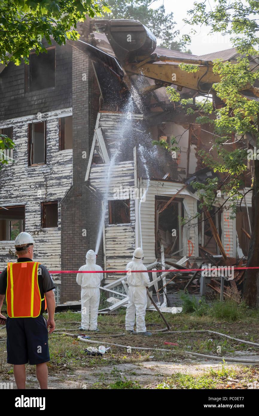 Detroit, Michigan - uso abbigliamento protettivo per la protezione contro l'esposizione all'amianto, lavoratori demolire una casa abbandonata. Essi spruzzare acqua sulla sede, Immagini Stock