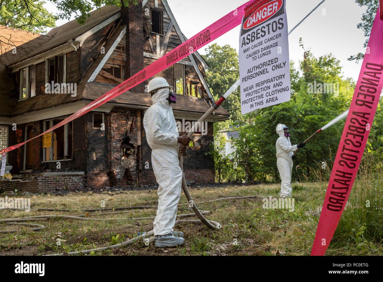 Detroit, Michigan - uso abbigliamento protettivo per la protezione contro l'esposizione all'amianto, lavoratori demolire le case abbandonate. Essi spruzzare acqua su edifici Immagini Stock