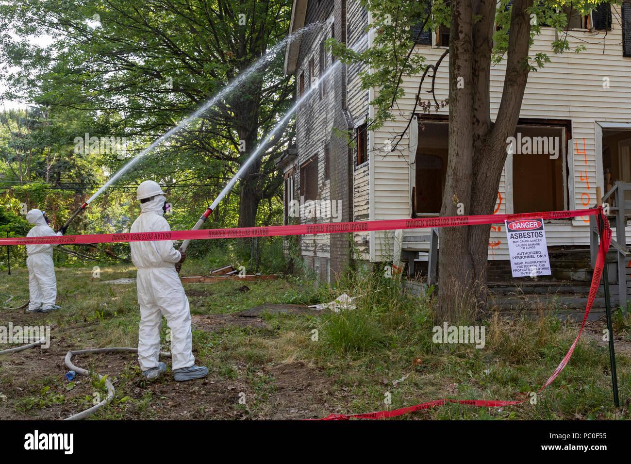 Detroit, Michigan - uso abbigliamento protettivo per la protezione contro l'esposizione all'amianto, lavoratori preparare per la demolizione di una casa abbandonata. Essi spruzzare acqua sul Immagini Stock