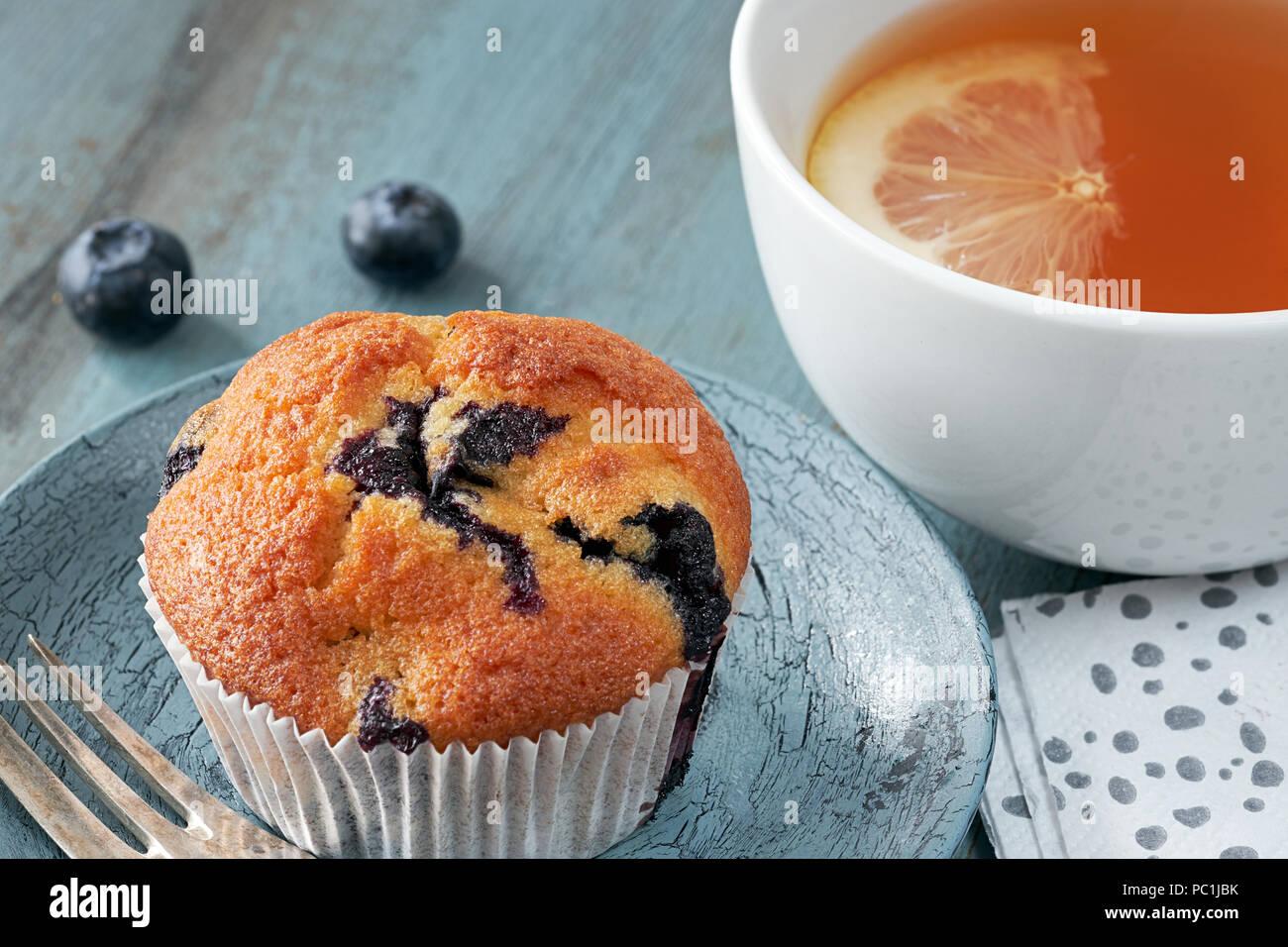 Close-up su muffin ai mirtilli e la tazza di tè con limone su grigio rustico tavolo in legno Immagini Stock