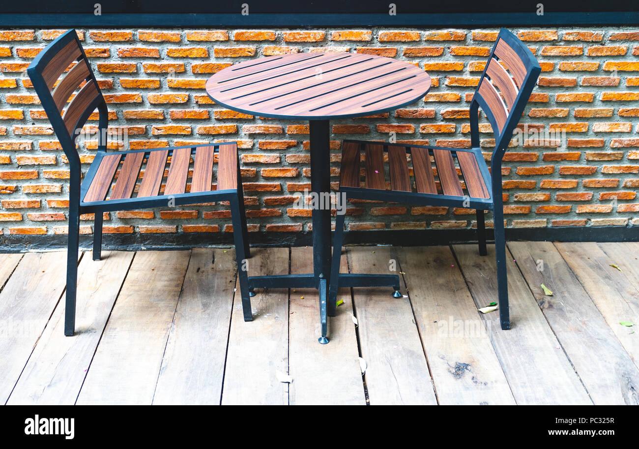 Close up con sedie in legno e la tavola rotonda sulla massa di legno ...