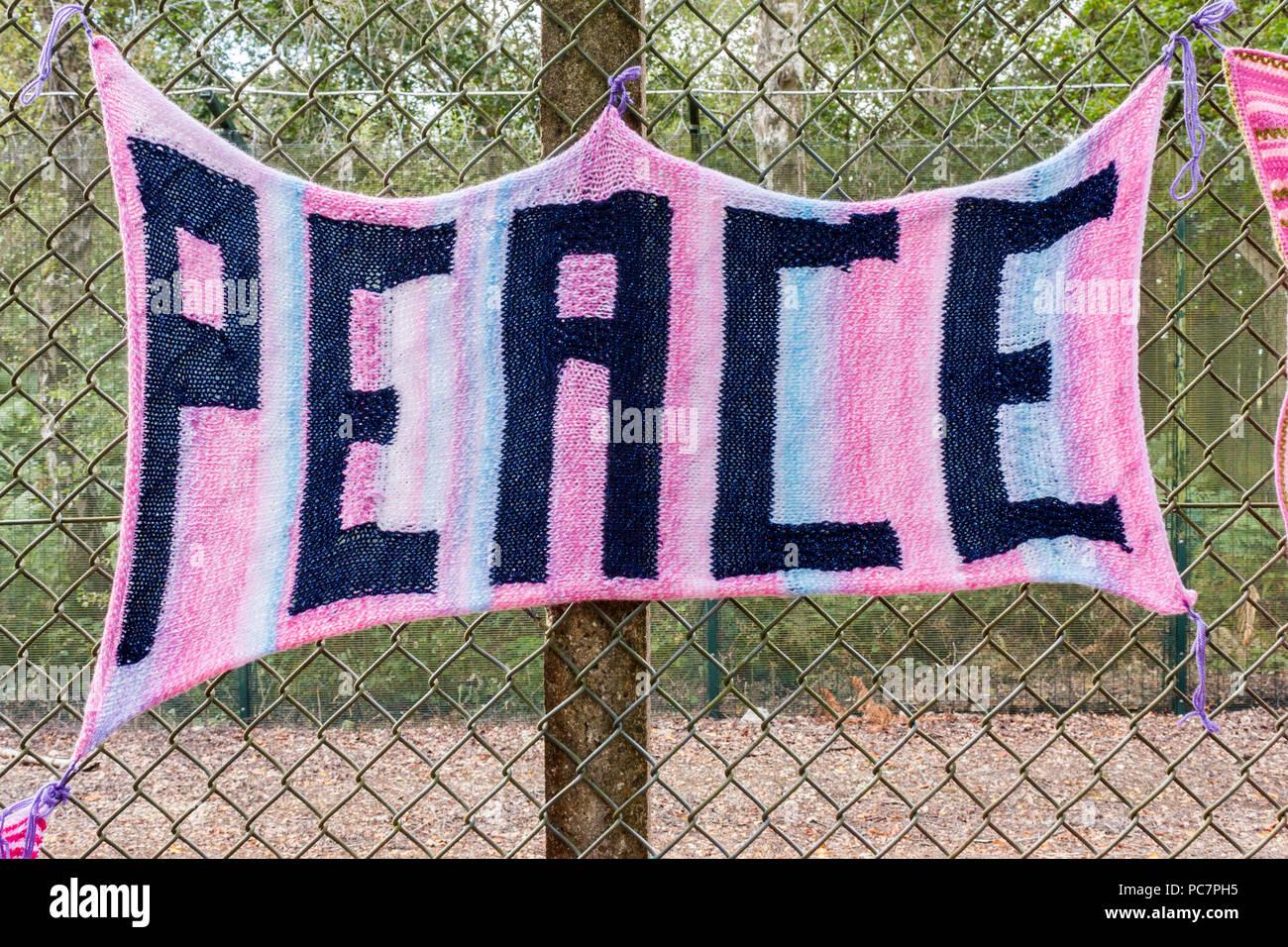 Sciarpa lavorata a maglia con la parola 'pace' su di essa legata a un recinto sul perimetro delle armi atomiche stabilimento a Aldermaston, Berkshire, Inghilterra, GB. Immagini Stock