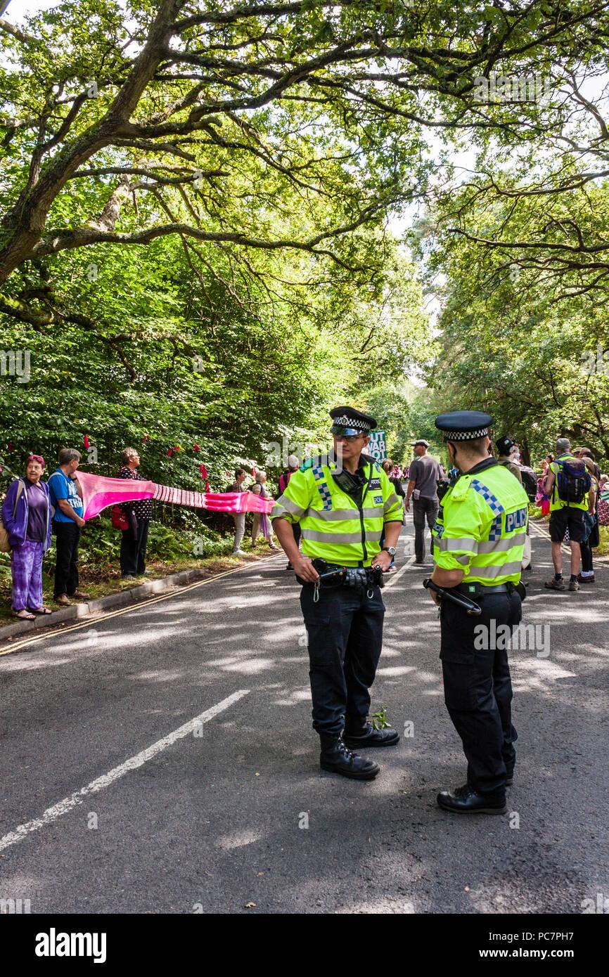 La polizia in servizio presso una protesta pacifica dai membri e sostenitori della campagna per il disarmo nucleare (CND) vicino AWE, Aldermaston. Immagini Stock