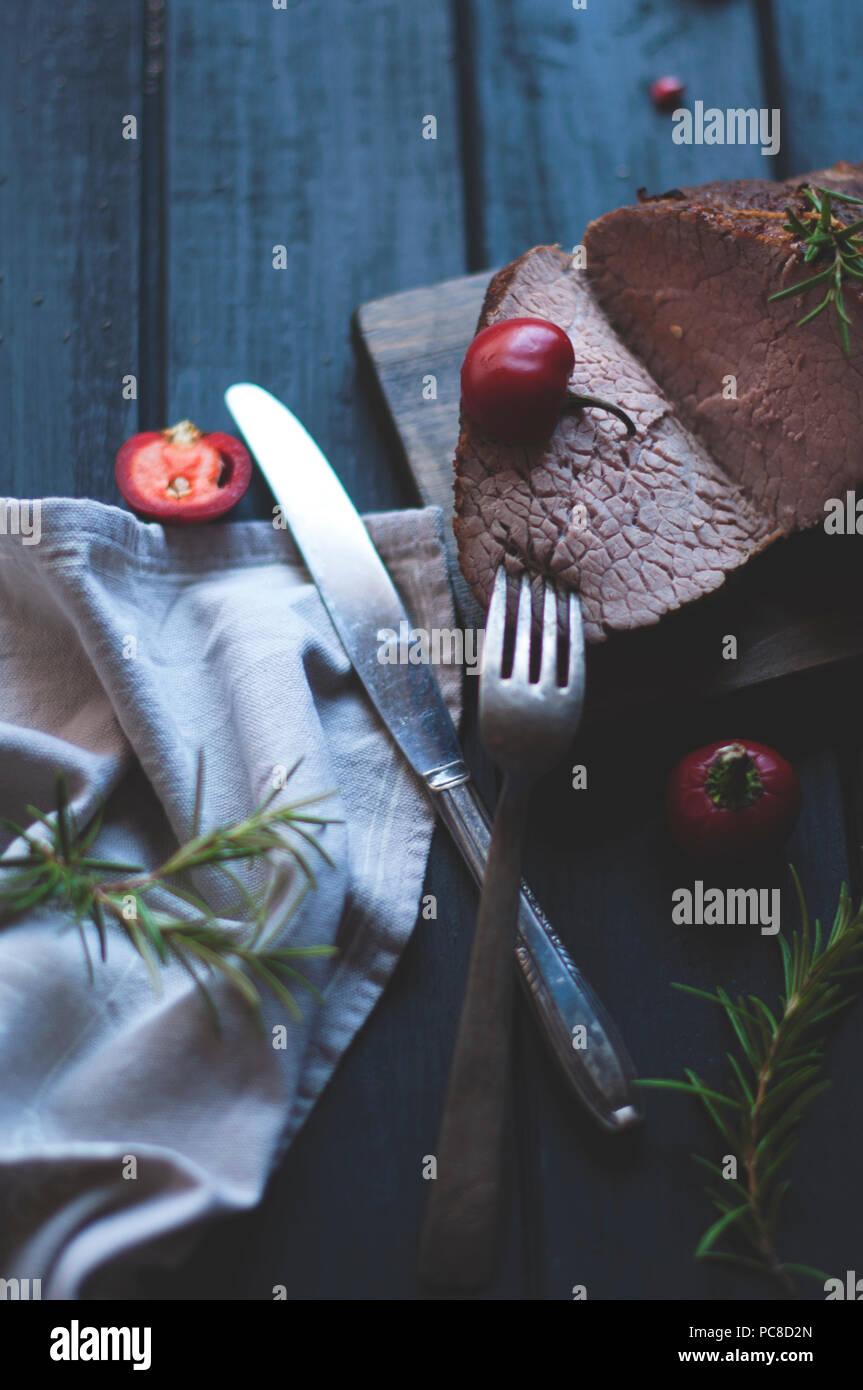 Carni cotte al forno con rosmarino e pepe rosso. Bistecca di manzo. Cena per gli uomini. foto scura. Sfondo nero. pannello di legno Immagini Stock