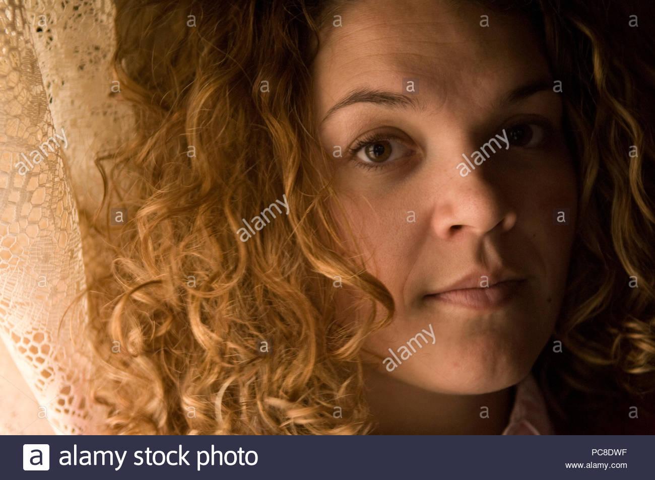 Ritratto di una giovane donna con capelli ricci. Immagini Stock