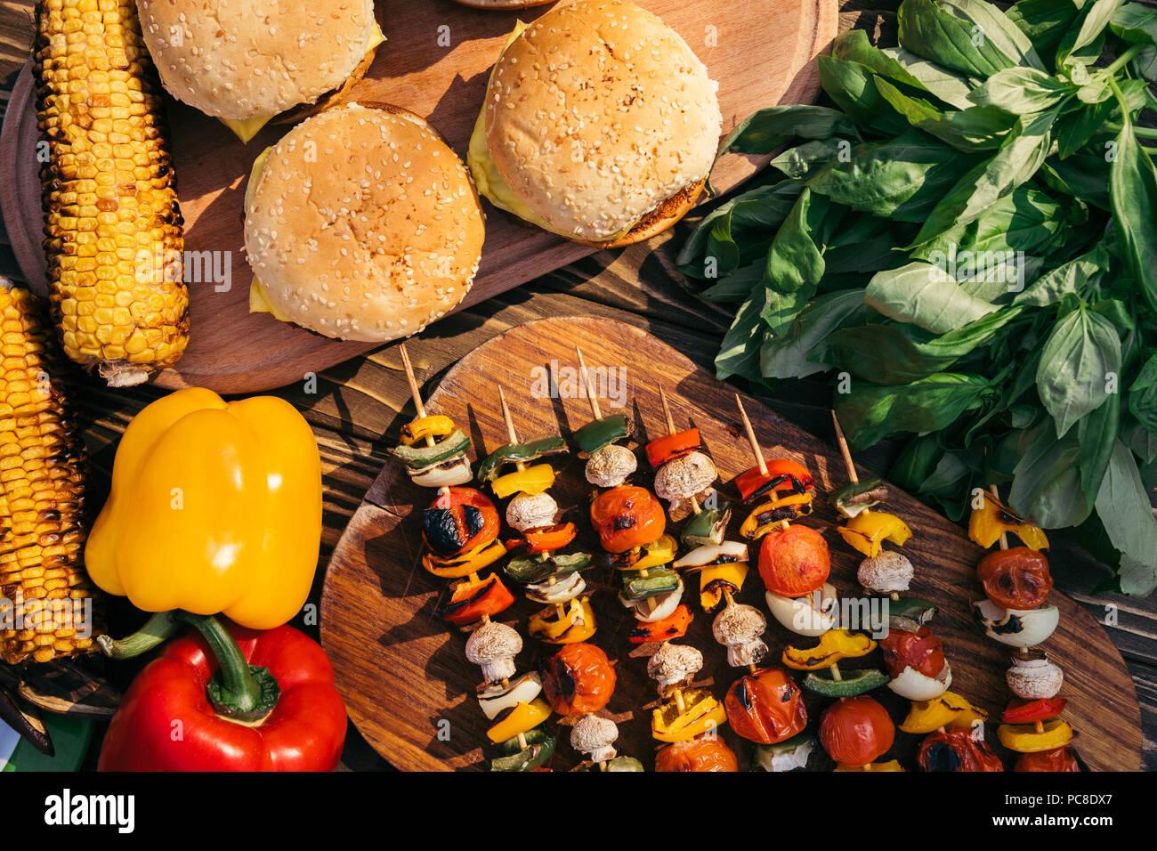 Su vegetali spiedini e hamburger grigliati per barbecue all'aperto Immagini Stock