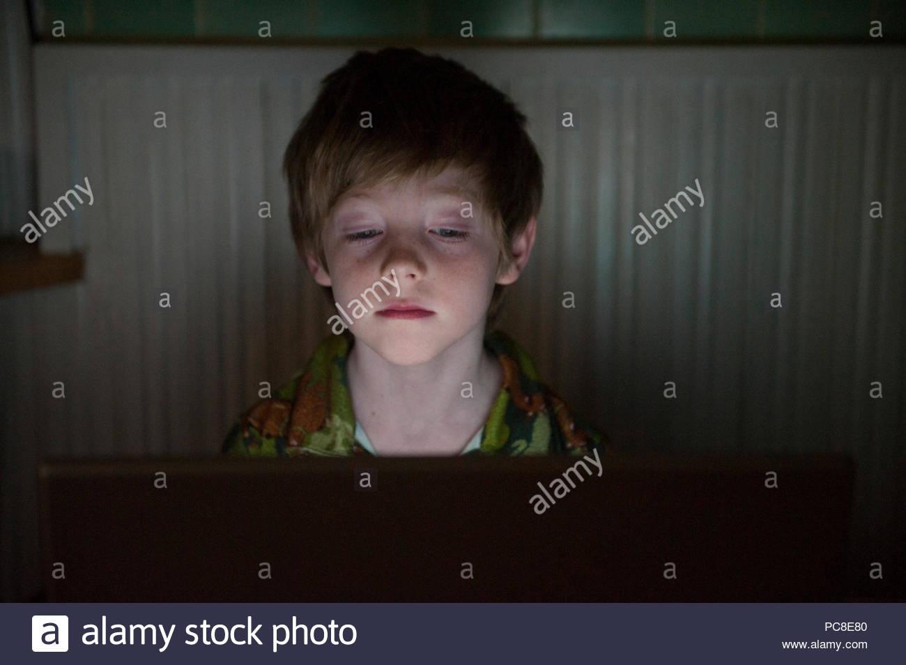 Un 7-anno-vecchio ragazzo nottambulo i giochi per computer. Immagini Stock