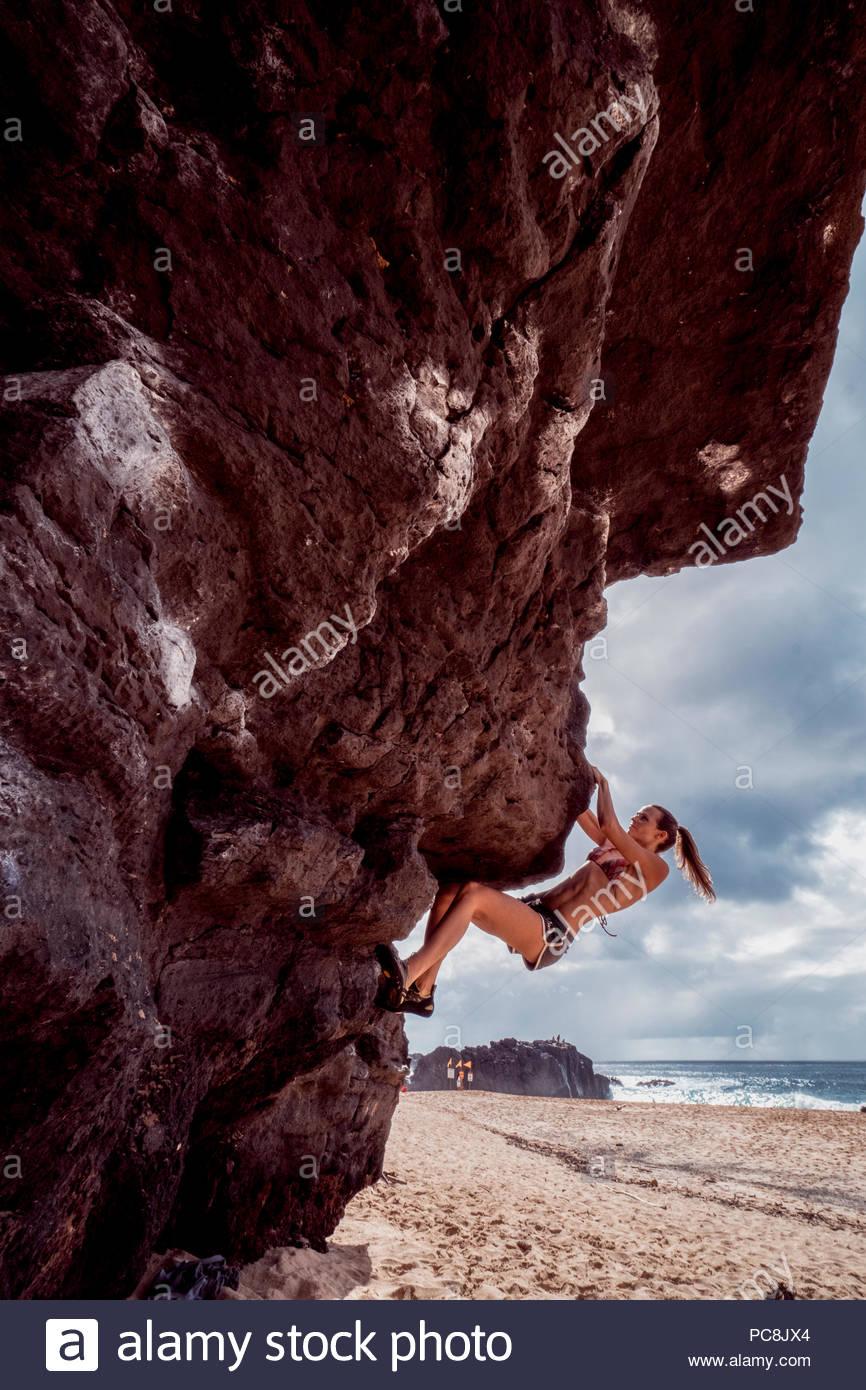 Una donna bouldering sulla spiaggia nelle Hawaii. Immagini Stock