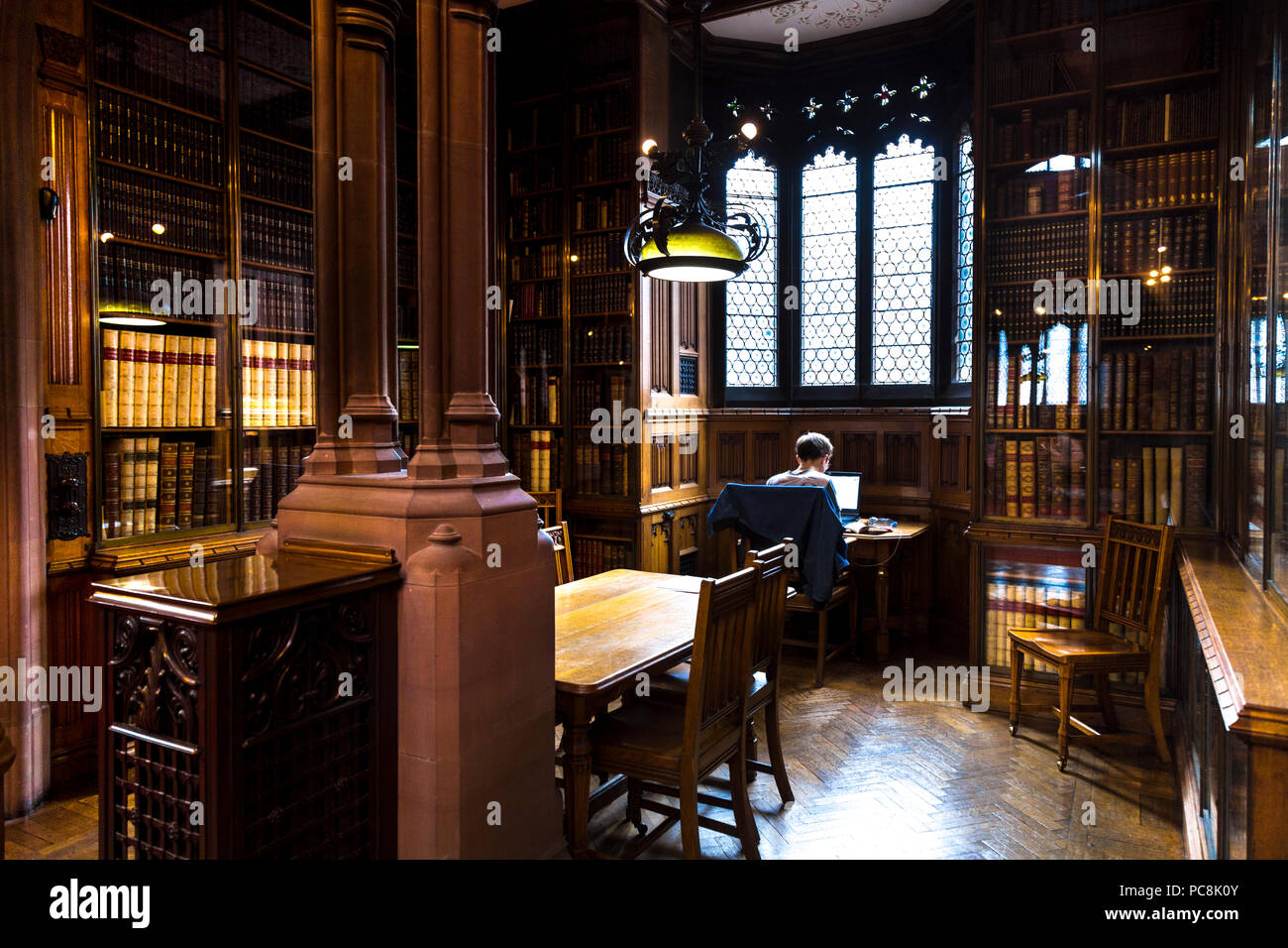 Uomo seduto con un laptop a una vecchia libreria facendo ricerca, studiare, Johny Rylands Library, Manchester, Regno Unito Immagini Stock