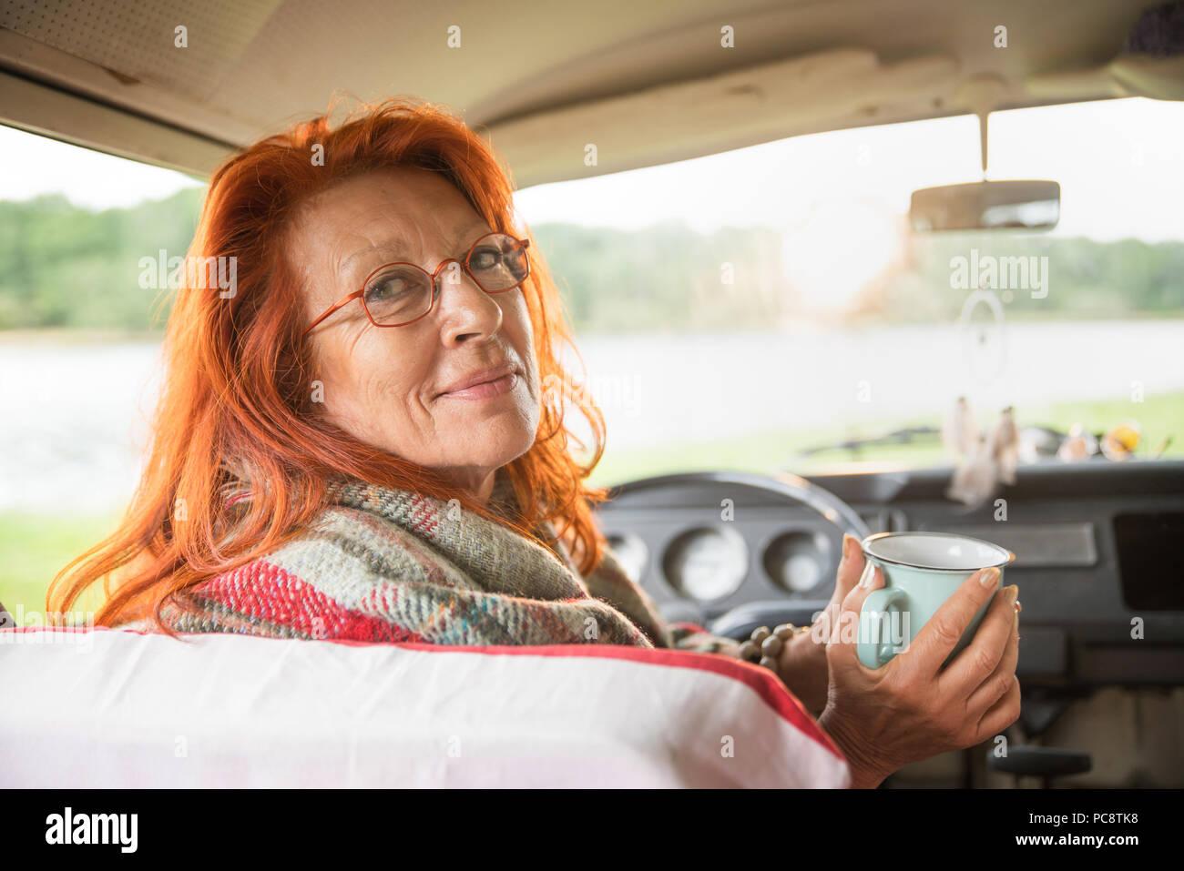 Senior hipster donna nella sua van guardando la fotocamera Immagini Stock