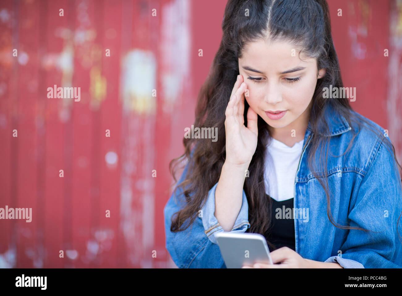 Ragazza adolescente vittima di bullismo mediante messaggio di testo all'aperto Immagini Stock