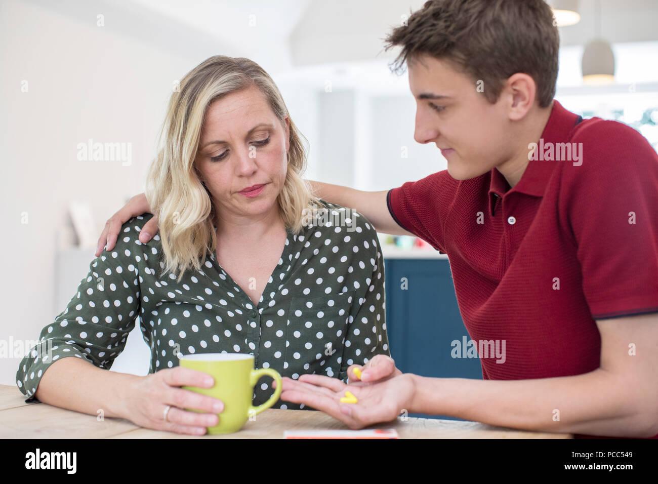 Figlio adolescente genitore aiuta la sofferenza con problemi di salute mentale con la medicazione Immagini Stock