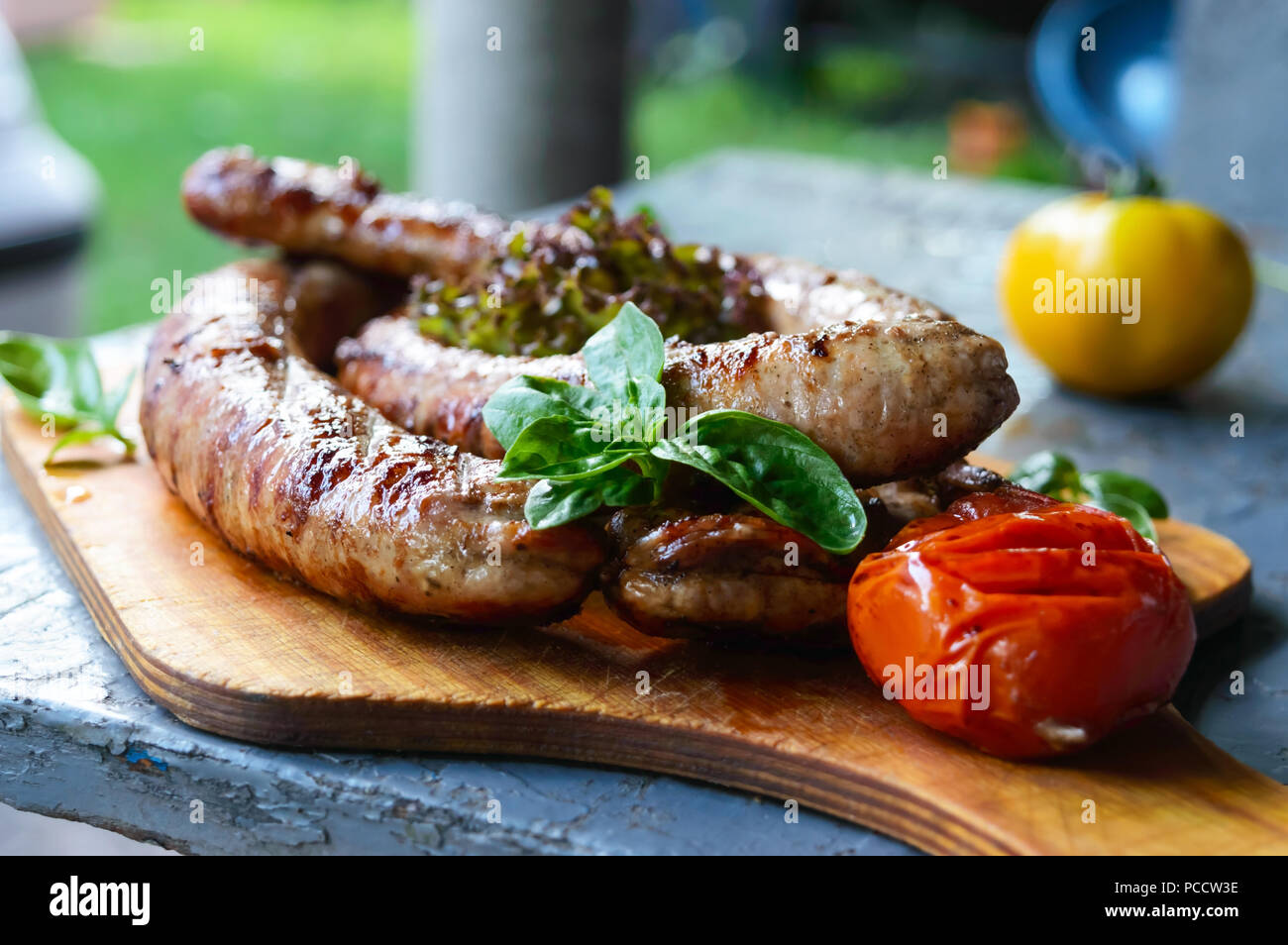 Salsicce di maiale fritto nel fuoco. Immagini Stock